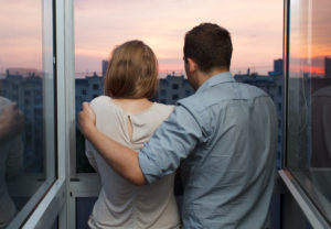 Young couple on the balcony at a high floor looking at city during sunset